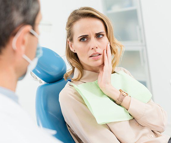 Woman at emergency dentistry visit holding cheek